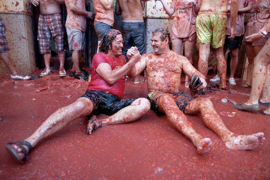 Revelers are covered in tomato pulp while participating the annual Tomatina festival on Wednesday in Bunol, Spain. Thousands of people threw 120 tons of ripe tomatoes in the world's biggest tomato fight held annually in this Spanish Mediterranean town.  (Photo by Pablo Blazquez Dominguez/Getty Images) Photo: Pablo Blazquez Dominguez, Ap/getty / 2012 Getty Images