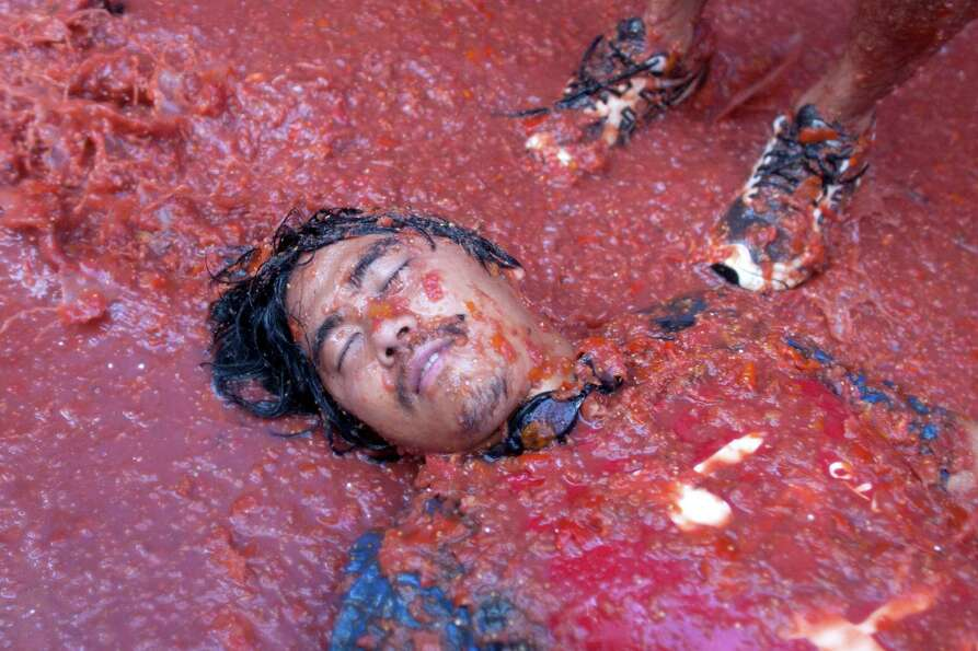 :  A reveler lays on tomato pulp while participating in the annual Tomatina festival on Wednesday in