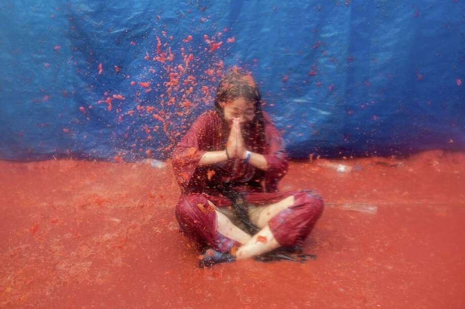 A Japanese girl sits in tomato pulp while participating in the annual Tomatina festival on Wednesday in Bunol, Spain. Thousands of people people throw 120 tons of ripe tomatoes in the world's biggest tomato fight held annually in this Spanish Mediterranean town.  (Photo by Pablo Blazquez Dominguez/Getty Images) Photo: Pablo Blazquez Dominguez, Ap/getty / 2012 Getty Images