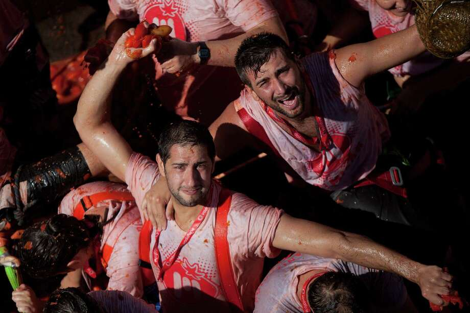 Revelers throw tomatoes during the annual Tomatina festival on Wednesday in Bunol, Spain. thousands of people throw 120 tons of ripe tomatoes in the world's biggest tomato fight held annually in this Spanish Mediterranean town.  (Photo by Pablo Blazquez Dominguez/Getty Images) Photo: Pablo Blazquez Dominguez, Ap/getty / 2012 Getty Images