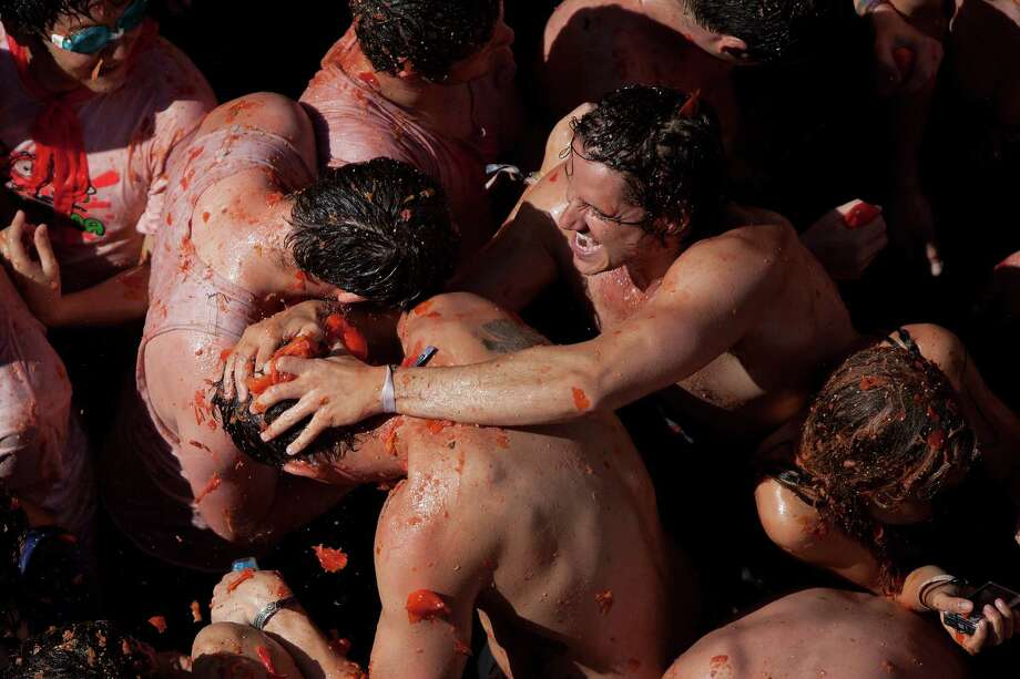 Revelers throw tomatoes at each other during the annual Tomatina festival on Wednesday in Bunol, Spain. Thousands of people people throw 120 tons of ripe tomatoes in the world's biggest tomato fight held annually in this Spanish Mediterranean town.  (Photo by Pablo Blazquez Dominguez/Getty Images) Photo: Pablo Blazquez Dominguez, Ap/getty / 2012 Getty Images