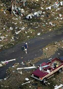 A man walks through a neighborhood damaged by Hurricane Katrina Wednesday, Aug. 31, 2005 in Gulfport, Miss. Photo: DAVID J. PHILLIP, AP / AP