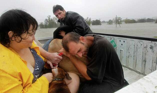 Residents who were rescued from their flooded homes are transported to waiting assistance, after Hurricane Isaac made landfall and flooded homes with 10 feet of water in Braithwaite, La., Wednesday, Aug. 29, 2012.  Isaac was packing 80 mph winds, making it a Category 1 hurricane. It came ashore early Tuesday near the mouth of the Mississippi River, driving a wall of water nearly 11 feet high inland and soaking a neck of land that stretches into the Gulf.  (AP Photo/Gerald Herbert) Photo: Gerald Herbert, Associated Press / AP