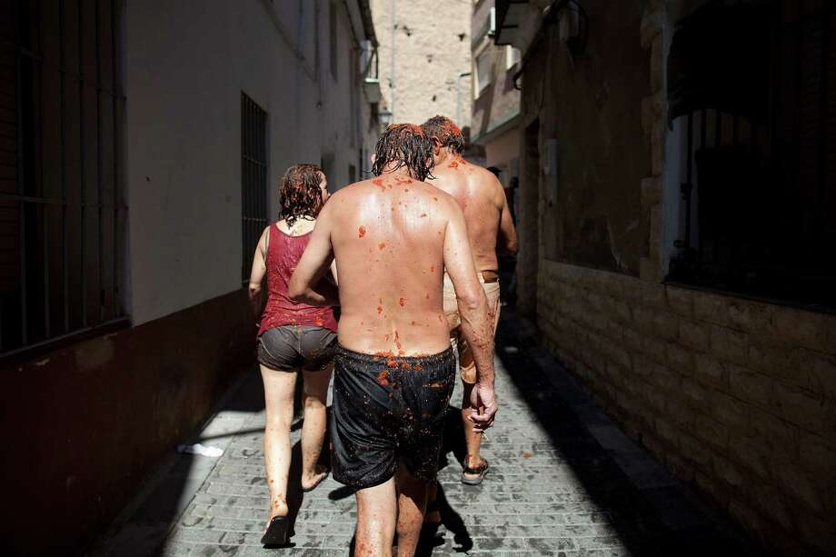 BUNOL, SPAIN - AUGUST 29:  Revellers walk away from tomato fights during the annual Tomatina festival on August 29, 2012 in Bunol, Spain. An estimated 35,000 people threw 120 tons of ripe tomatoes in the world's biggest tomato fight held annually in this Spanish Mediterranean town. Photo: Pablo Blazquez Dominguez, Getty Images / 2012 Getty Images