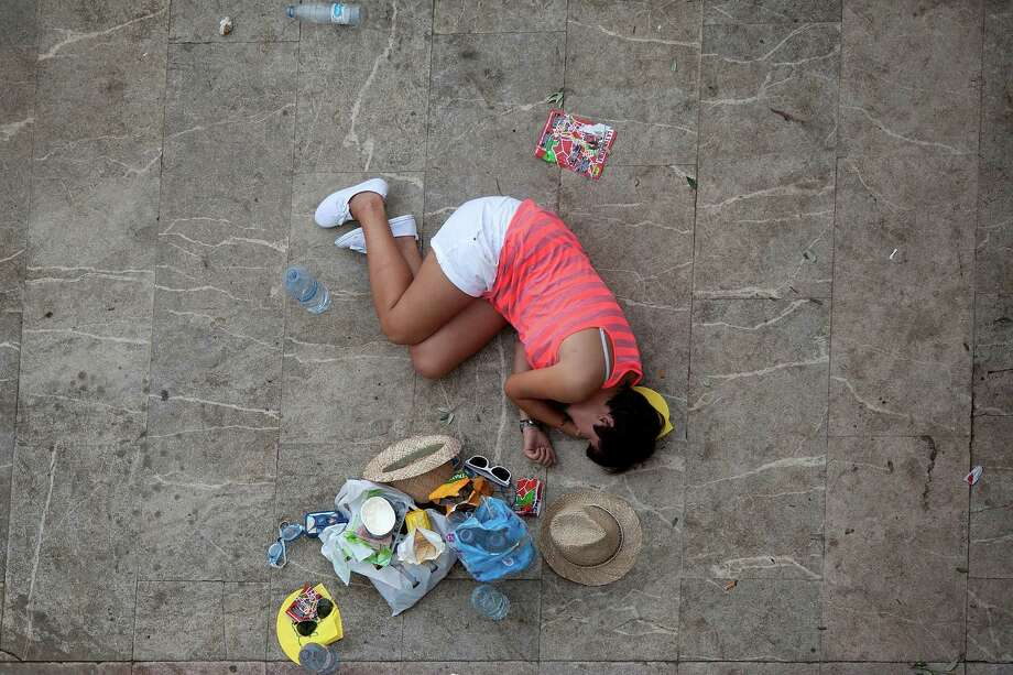 BUNOL, SPAIN - AUGUST 29:  A reveller sleeps waiting for the annual Tomatina festival on August 29, 2012 in Bunol, Spain. An estimated 35,000 people throw 120 tons of ripe tomatoes in the world's biggest tomato fight held annually in this Spanish Mediterranean town. Photo: Pablo Blazquez Dominguez, Getty Images / 2012 Getty Images
