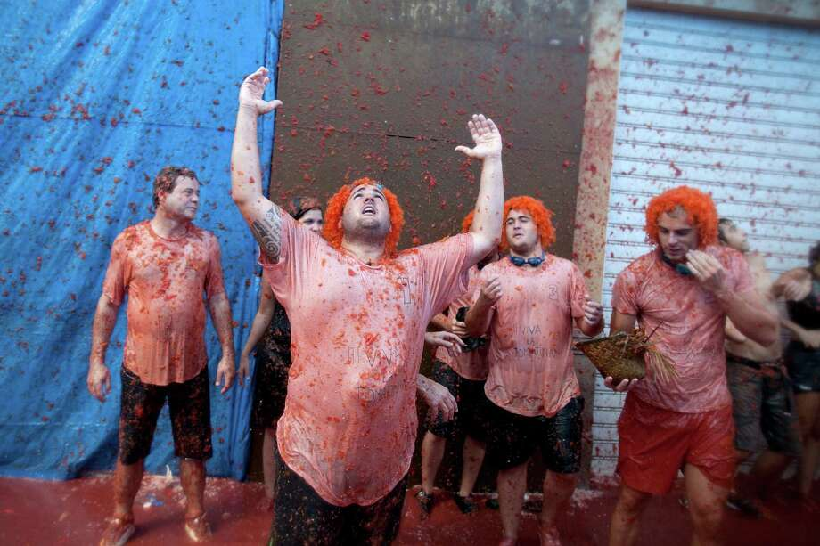 BUNOL, SPAIN - AUGUST 29:  Revelers are covered in tomato pulp while participating the annual Tomatina festival on August 29, 2012 in Bunol, Spain. An estimated 35,000 people threw 120 tons of ripe tomatoes in the world's biggest tomato fight held annually in this Spanish Mediterranean town. Photo: Pablo Blazquez Dominguez, Getty Images / 2012 Getty Images