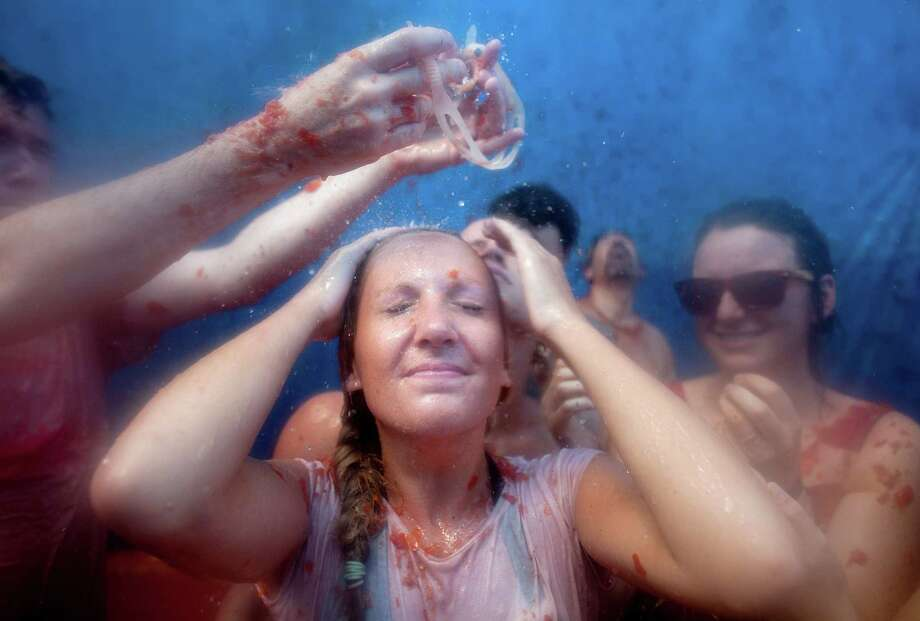 BUNOL, SPAIN - AUGUST 29:  A girl stands under water during the annual Tomatina festival on August 29, 2012 in Bunol, Spain. An estimated 35,000 people throw 120 tons of ripe tomatoes in the world's biggest tomato fight held annually in this Spanish Mediterranean town. Photo: Pablo Blazquez Dominguez, Getty Images / 2012 Getty Images