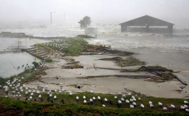 Sea birds surround the American Legion fishing pier in Bay St. Louis, Miss., as Isaac's winds and storm surge flood some low laying neighborhoods, Wednesday, Aug. 29, 2012, the seventh  anniversary of Hurricane Katrina hitting the Gulf Coast. Isaac was packing 80 mph winds, making it a Category 1 hurricane. It came ashore early Tuesday near the mouth of the Mississippi River, driving a wall of water nearly 11 feet high inland and soaking a neck of land that stretches into the Gulf. (AP Photo/Rogelio V. Solis) Photo: Rogelio V. Solis, Associated Press / AP