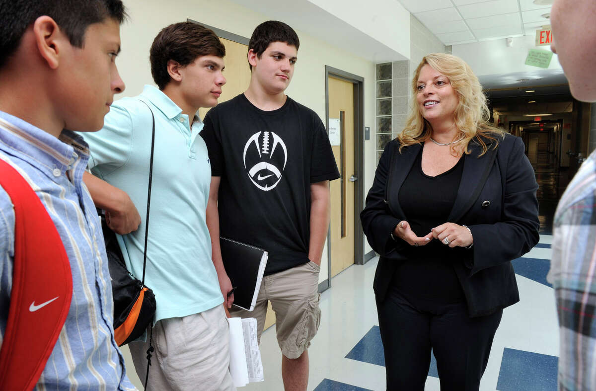 Stacey Gross, right, the new principal of Ridgefield High School, talks to kids in the hallway on the first day of school, Wed. Sept. 29, 2012. They are, from left, Ryan Dillon, Austin Pavone and Matthew Saporito, all 14-year-old freshmen.