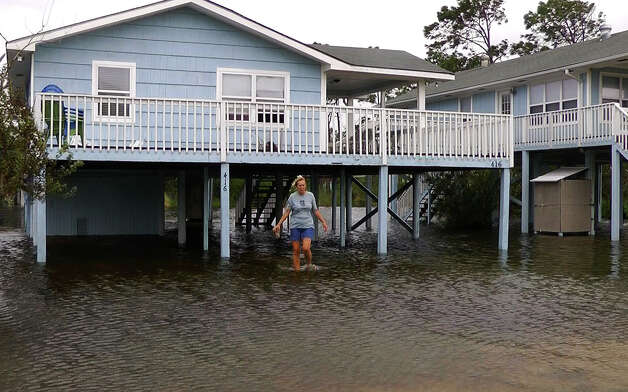 Gina Johnson wades through her front yard in Gulf Shores, Ala., on Wednesday, Aug. 29, 2012, after the coastal town took a glancing blow from Hurricane Isaac as it made landfall in Louisiana. While the storm brought heavy rain and wind to the Alabama coast, little significant damage was reported. (AP Photo/Jay Reeves) Photo: Jay Reeves, Associated Press / AP