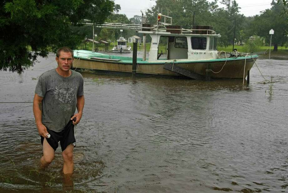 Matt Lischke walks through the knee-high flood waters of Bayou Coden after checking on two of his boats and the boat of a friend Wednesday, Aug. 29, 2012 in Coden, Ala. as Isaac makes landfall along the Gulf Coast.  Isaac, downgraded to a tropical storm, has top sustained winds of 70 mph (112 kph), just below the hurricane threshold of 74 mph (119 kph). The storm is about 50 miles (80 kilometers) west-southwest of New Orleans, where it is bringing drenching rains and fierce winds. (AP Photo/Mobile Register, G.M. Andrews) MAGS OUT Photo: G.M. ANDREWS, Associated Press / Mobile Register