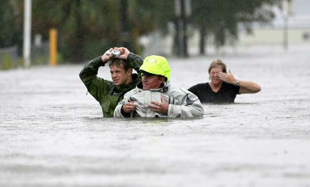 Chuck Cropp, center, his son Piers, left, and wife Liz, right, wade through floodwaters from Hurricane Isaac Wednesday, Aug. 29, 2012, in New Orleans. As Isaac made landfall, it was expected to dump as much as 20 inches of rain in several parts of Louisiana. (AP Photo/David J. Phillip) Photo: David J. Phillip, Associated Press / AP