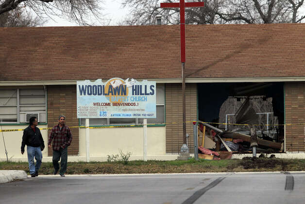 Pastor Paul Gonzales (left) and Jerry Salinas walk in front of Woodlawn Hills Baptist Church Wednesday January 23, 2013. San Antonio police officer Matthew Porter said a witness called police about 2:00 a.m. after seeing an accident at West Woodlawn and Maiden Lane. Porter said a car went through a stop sign and hit a curb, then went airborne and into the outside wall of the single-story building. Damages to the building are estimated at $30,000. Photo: JOHN DAVENPORT, San Antonio Express-News / ©San Antonio Express-News/Photo Can Be Sold to the Public