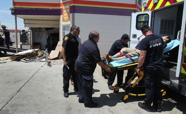 San Antonio paramedics prepare to transport the driver of a Chevy Trailblazer Wednesday August 29, 2012 after he crashed his vehicle into the office of the Public Storage facility on the 2400 block of South Hackberry.  Police said the driver of the vehicle had a seizure while driving, causing him to lose control of the vehicle. Nobody inside the building was injured. Photo: John Davenport, San Antonio Express-News / San Antonio Express-News