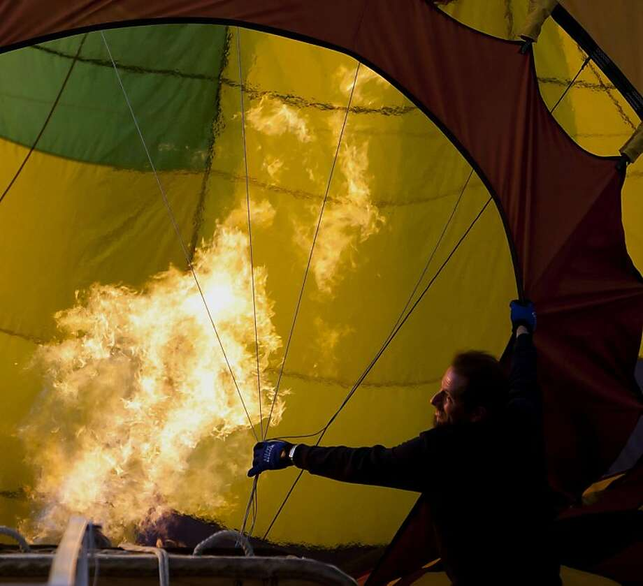 Jack Newberry keeps the guide lines tight as a hot air balloon is heated with a propane blower, Wednesday, August 29, 2012 at Ann Morrison Park during the annual Spirit of Boise Balloon Classic in Boise, Idaho. (Darin Oswald/Idaho Statesman/MCT) Photo: Darin Oswald, McClatchy-Tribune News Service