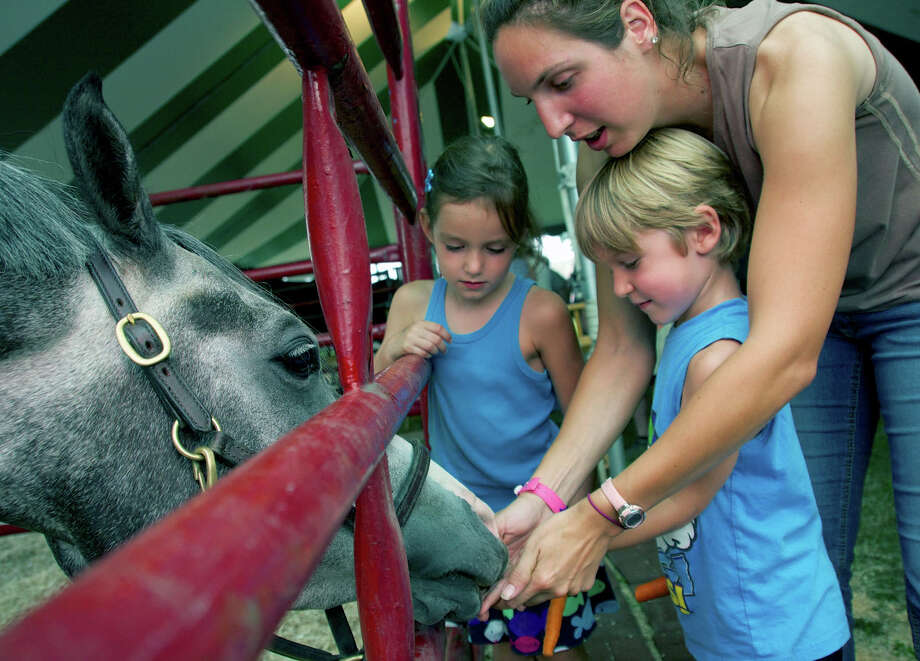 James and Clara D'Amico of New Milford are helped feeding a carrot to their horse, Chip, by trainer Michele Lomba of Roxbury James D'Amico (up front with carrot) and Clara D'Amico.  Michele Lomba (from Roxbury) is Chips trainer and a trainer at Trowbridge's (in Bridgewater) Photo: Trish Haldin