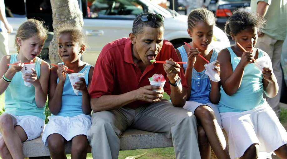 In this Aug. 13, 2008 file photo, Democratic presidential candidate Sen. Barack Obama, D-Ill., eats shaved ice with his daughters Sasha Obama, 7, second from left, and Malia Obama, 10, second from right, and unidentified friends in Kailua, Hawaii for a vacation. Photo: Alex Brandon / AP
