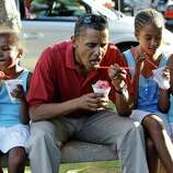 In this Aug. 13, 2008 file photo, Democratic presidential candidate Sen. Barack Obama, D-Ill., eats shaved ice with his daughters Sasha Obama, 7, second from left, and Malia Obama, 10, second from right, and unidentified friends in Kailua, Hawaii for a vacation.