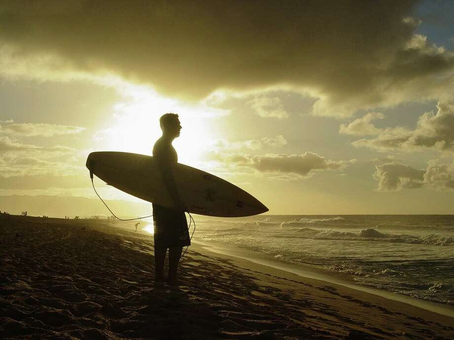 """A surfer in Hawaii """"eclipses"""" the sun from the photographer -- but not with the kind of drama and exhilaration that happens when the moon does it. ( April Orcutt -- all rights reserved) Photo: April Orcutt / © April Orcutt – all rights reserved"""