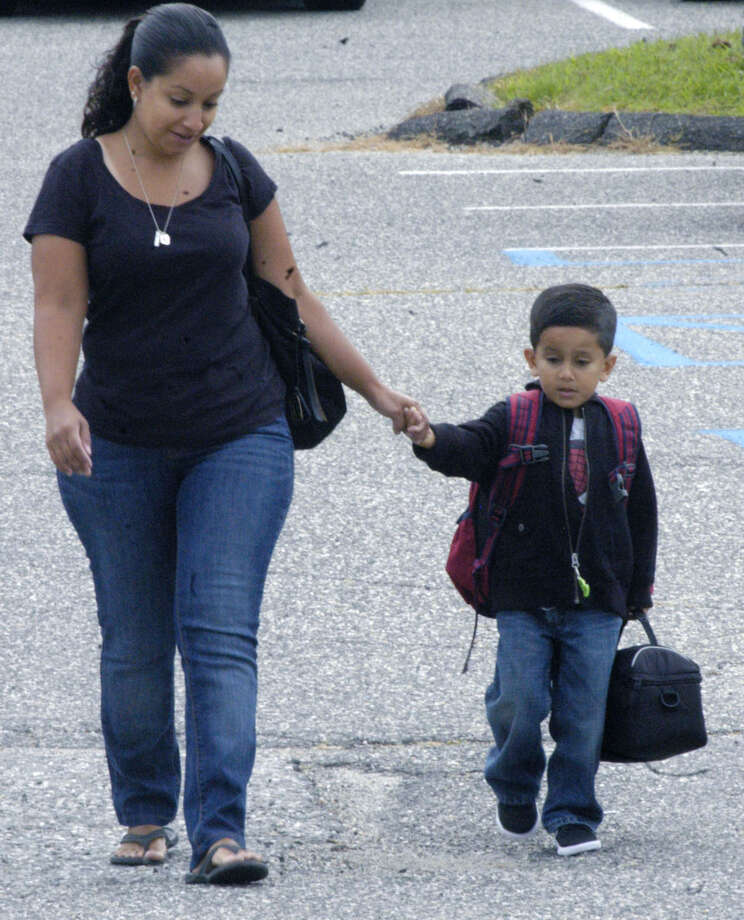 Logan Cardenas, 4, of New Milford hangs on perhaps ever more tightly to the hand of his mom, Eliza Cardenas, as he gets closer to the school on opening dayat Northville School. Logan, a kindergartner, was among the more than 5,000  students to start their 2012-13 school year Monday, Aug. 27, 2012. Photo: Norm Cummings