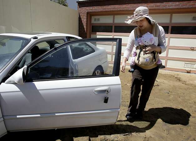 Amy Hung, with son Stephen, examines her Honda that was parked at her father's house. Photo: Brant Ward, The Chronicle