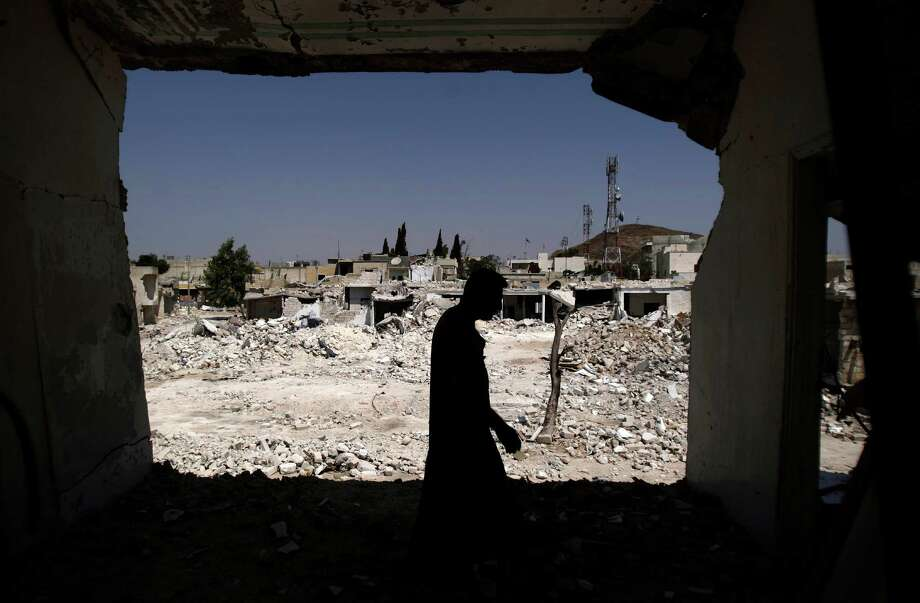 A Syrian man walks in his house which was destroyed in a Syrian government forces shelling, over looking the rubble of other houses, in Azaz, on the outskirts of Aleppo, Syria, Wednesday, Aug. 29, 2012. (AP Photo/Muhammed Muheisen) Photo: Muhammed Muheisen / AP