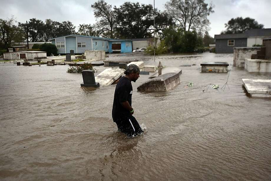 OAKVILLE, LA - AUGUST 29:  Errol Ragas walks past a cemetery to recover dry blankets from his home as rising waters from Hurricane Isaac flood his neighborhood on August 29, 2012 in Oakville, in Plaquemines Parish, Louisiana. The parish, south of New Orleans, was the most heavily damaged by the hurricane. The system, which was downgraded to a tropical storm by the National Weather Service, moved slowly across the state, dumping large amounts of rain and knocking out power to half a million Louisianans.  (Photo by John Moore/Getty Images) Photo: John Moore, Getty Images