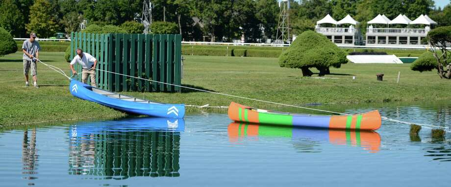 Two canoes painted in the colors of the dead heat winner's of the Travers Stakes were launched in to the infield lake of the Saratoga Race Course in Saratoga Springs, N.Y. Aug. 29, 2012.  The blue canoe represents the colors of Alpha who is owned Sheik Mohammed Al Maktoum of Dubai.  The multi-colored canoe is painted in the colors of Golden Ticket owned by Magic City Thoroughbred Investments.     (Skip Dickstein/Times Union) Photo: Skip Dickstein