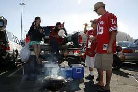 Evelyn Wang (far left) from Cupertino and Tanu Ghozh (middle) from San Jose take a seat on a truck while Tony Nguyen (middle) from Santa Clara and Matt Kinzer (right) from Campbell do some grilling while at the tailgate party at Candlestick Park parking lot in San Francisco , Calif., on Friday, August  10, 2012.