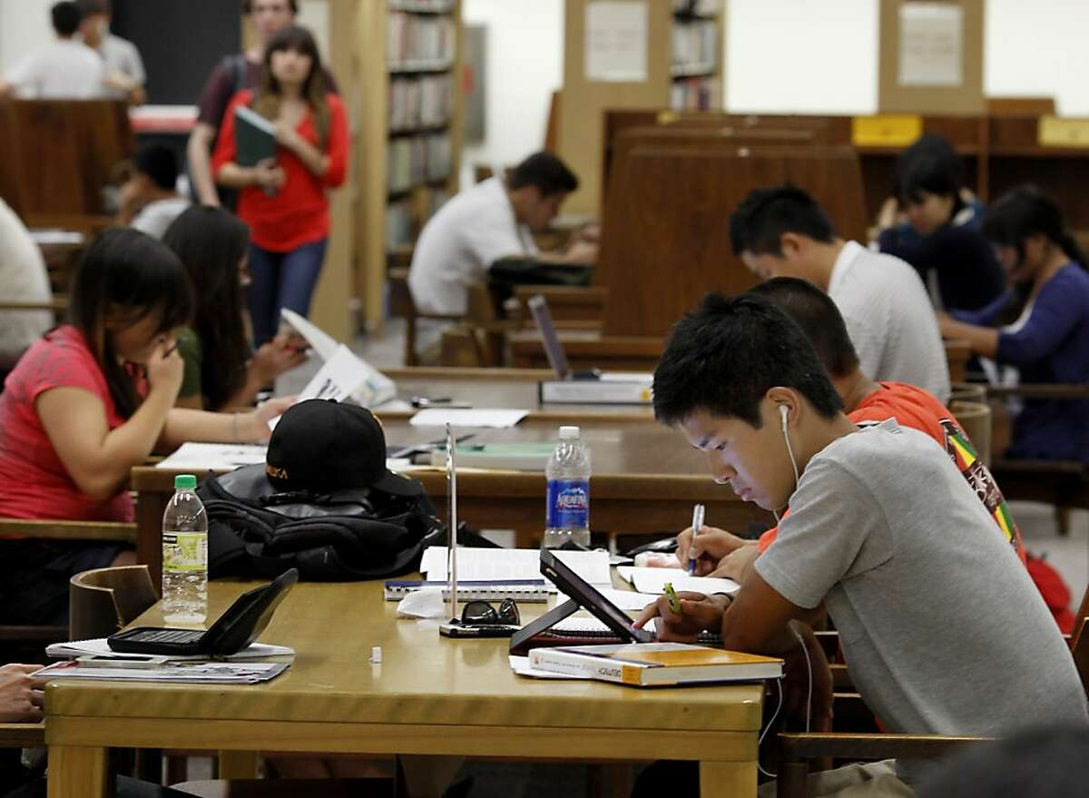 Kaito Saki (right) and others were busy in the library near the end of the day at Diablo Valley. Community Colleges like Diablo Valley Community College in Pleasant Hill, Calif. are losing students because of budget cuts resulting in fewer classes and fewer staff.