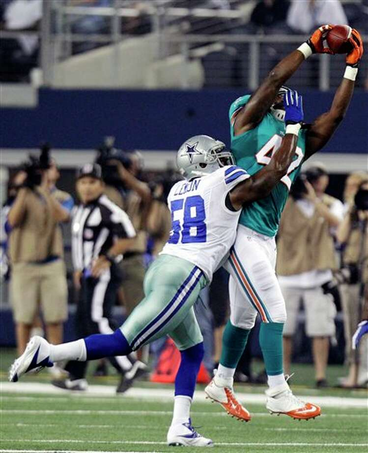 Miami Dolphins running back Charles Clay (42) makes a reception as Dallas Cowboys linebacker Orie Lemon (58) defends during the first half of a preseason NFL football game, Wednesday, Aug. 29, 2012, in Arlington, Texas. (AP Photo/LM Otero) Photo: LM Otero, Associated Press / AP