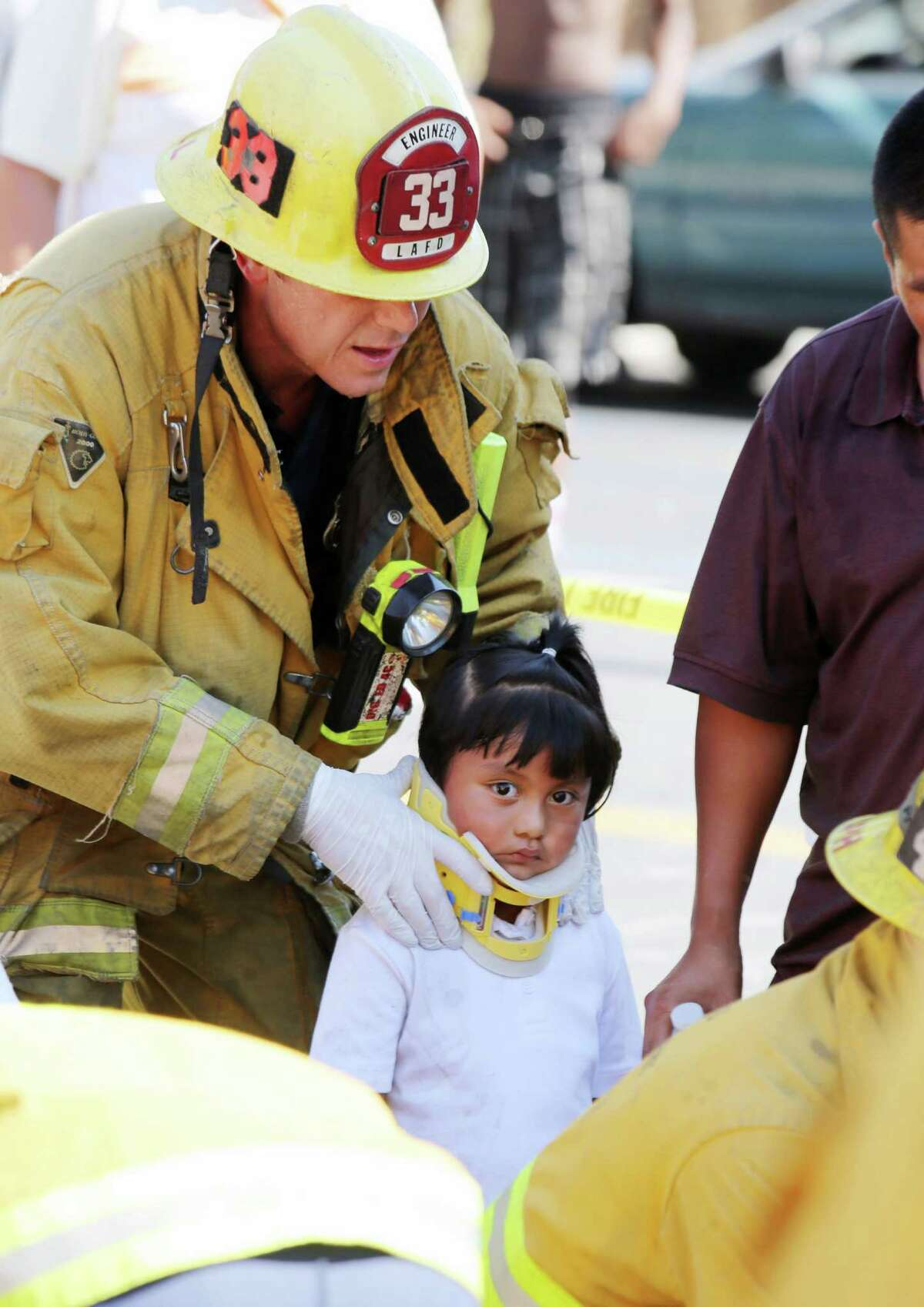 A Los Angeles City firefighter assists a child, one of eight people injured when a car sped onto a sidewalk and plowed into a group of parents and children outside Main Street Elementary school, Wednesday Aug. 29, 2012 in Los Angeles.