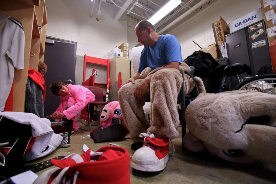 Mikey Springstead, left, and his father, Michael Springstead, right, gear up for their performances as mascots during a ValleyCats game on Saturday, August 25, 2012. (Erin Pihlaja / Special To The Times Union).