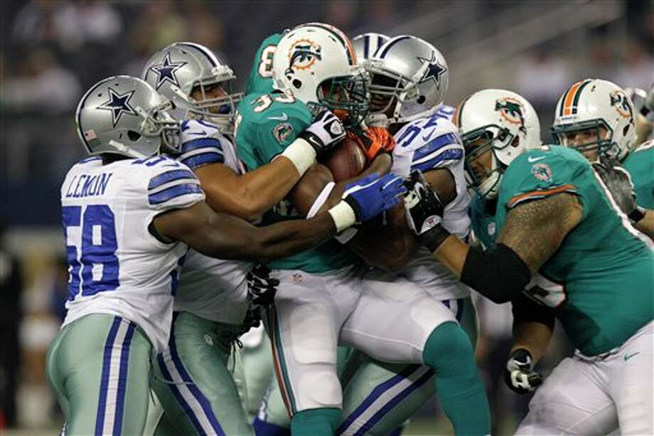 Miami Dolphins running back Daniel Thomas (33) is taken down by Dallas Cowboys' Orie Lemon (58) and Victor Butler (57) during a preseason NFL football game Wednesday, Aug. 29, 2012, in Arlington, Texas. (AP Photo/LM Otero) Photo: LM Otero, Associated Press / AP