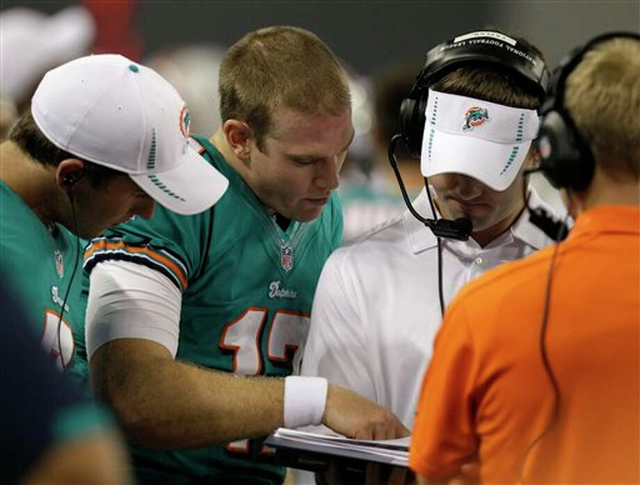 Miami Dolphins' Ryan Tannehill (17) with staff on the sideline during the first half of a preseason NFL football game against the Dallas Cowboys Wednesday, Aug. 29, 2012, in Arlington, Texas. (AP Photo/LM Otero) Photo: LM Otero, Associated Press / AP