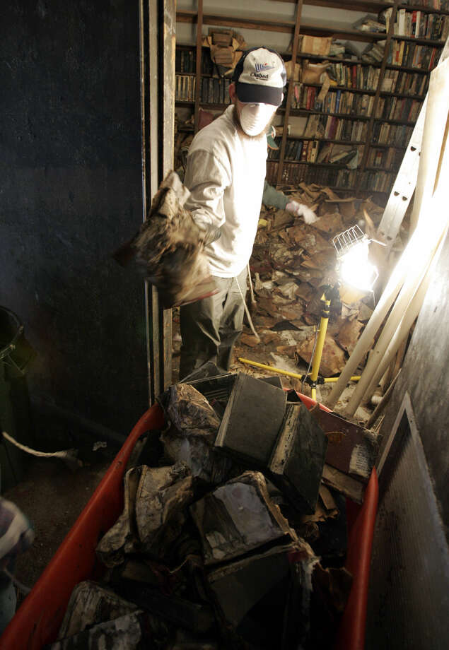 A volunteer collects Jewish holy books from a flood-damaged storeroom at Beth Israel synagogue in New Orleans Monday Dec. 19, 2005.  Dozens of Jewish college students are volunteering over winter break to clear out and properly dispose of holy texts and ritual items destroyed by Hurricane Katrina.  (AP Photo/Jacqueline Larma) Photo: JACQUELINE LARMA, ASSOCIATED PRESS / AP2005