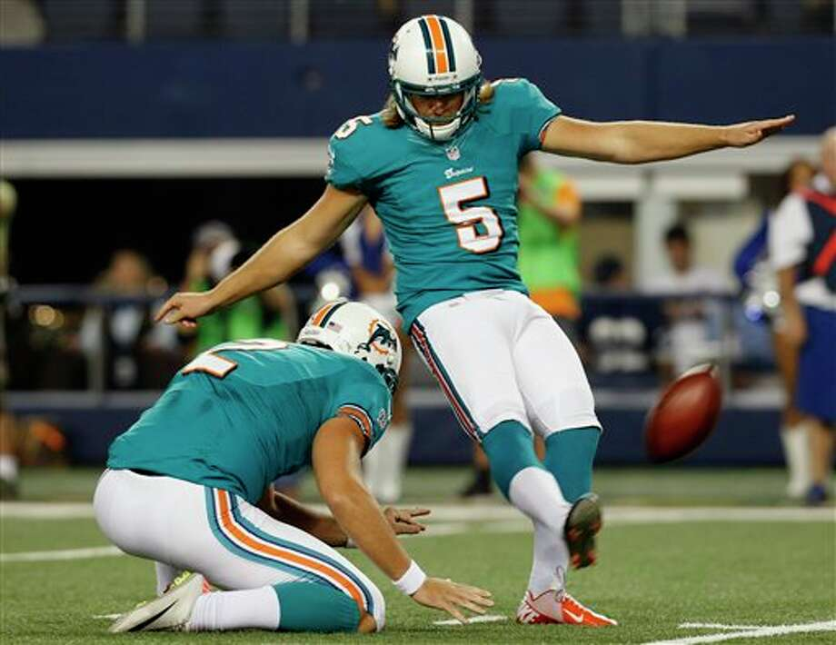 Miami Dolphins punter Brandon Fields holds for kicker Dan Carpenter (5) as he makes a field goal against the Dallas Cowboys during the first half of a preseason NFL football game, Wednesday, Aug. 29, 2012, in Arlington, Texas. (AP Photo/Sharon Ellman) Photo: Sharon Ellman, Associated Press / FR170032 AP