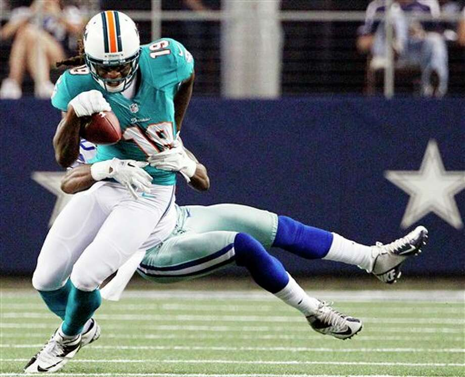 Dallas Cowboys cornerback Teddy Williams tackles Miami Dolphins wide receiver Legedu Naanee (19) during the first half of a preseason NFL football game, Wednesday, Aug. 29, 2012, in Arlington, Texas. (AP Photo/Tony Gutierrez) Photo: Tony Gutierrez, Associated Press / AP