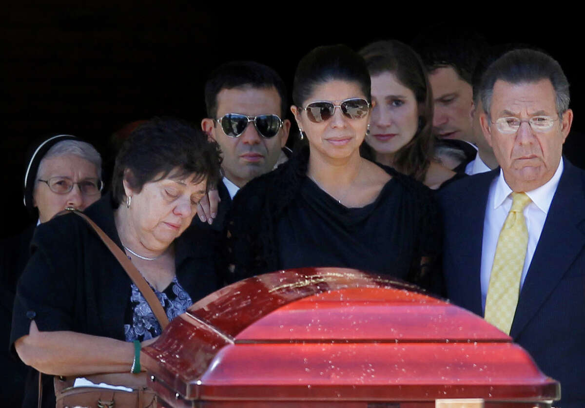 Ivette Rivera, center, fiancee of Empire State Building shooting victim Steve Ercolino, is flanked by the victim's parents, Rosalie and Frank Ercolino, as they follow the coffin out after a funeral mass at Our Lady of Sorrows church, Wednesday, Aug. 29, 2012, in White Plains, N.Y. The 41-year-old Ercolino was fatally shot in the head Friday by a former co-worker who blamed him for being laid off last year from a company with offices near the Empire State Building. (AP Photo/Jason DeCrow)