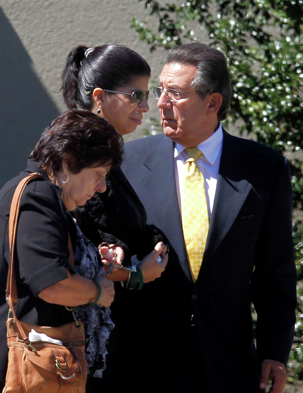 Ivette Rivera, center, fiancee of Empire State Building shooting victim Steve Ercolino, is flanked by the victim's parents, Rosalie and Frank Ercolino, as they walk to their car after a funeral mass at Our Lady of Sorrows church, Wednesday, Aug. 29, 2012, in White Plains, N.Y. The 41-year-old Ercolino was fatally shot in the head Friday by a former co-worker who blamed him for being laid off last year from a company with offices near the Empire State Building. (AP Photo/Jason DeCrow)