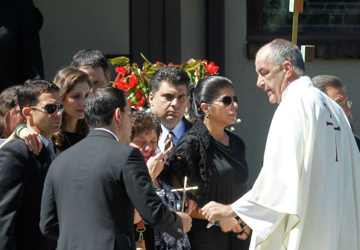 Friends and family of Empire State Building shooting victim Steve Ercolino, including his fiancee Ivette Rivera, second right, and his brother and mother Paul and Rosalie Ercolino, third and fourth right, leave after a funeral mass at Our Lady of Sorrows church, Wednesday, Aug. 29, 2012, in White Plains, N.Y. The 41-year-old Ercolino was fatally shot in the head Friday by a former co-worker who blamed him for being laid off last year from a company with offices near the Empire State Building. (AP Photo/Jason DeCrow)