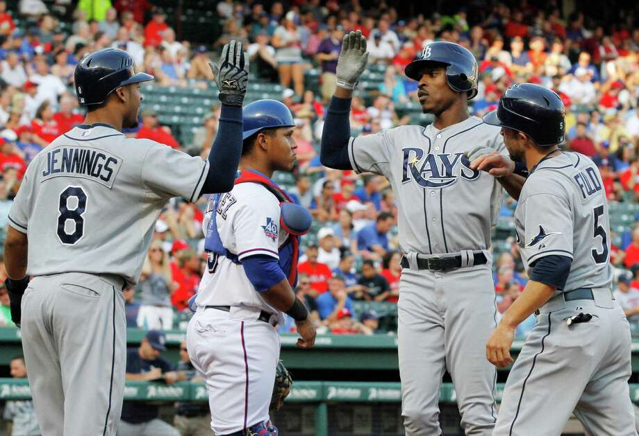 B.J. Upton (second from right) is congratulated by his Rays teammates after belting a three-run homer against Texas' Matt Harrison, who has struggled against Tampa Bay. Photo: Tim Sharp, Associated Press / FR62992 AP