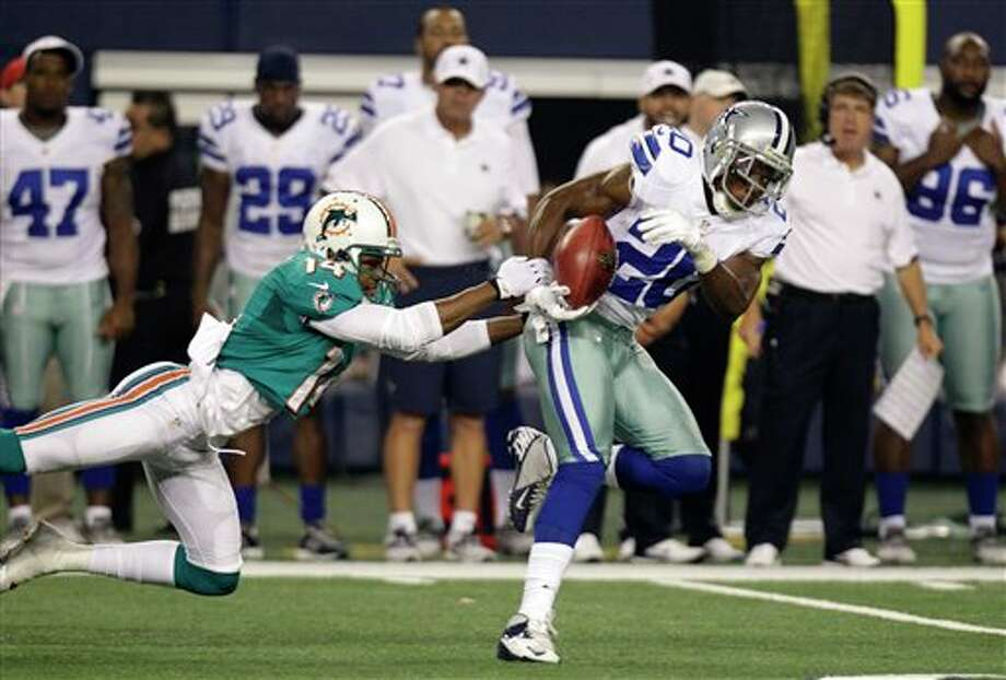 Miami Dolphins wide receiver Marlon Moore (14) attempts to stop Dallas Cowboys' Teddy Williams (20) in the first half of a preseason NFL football game Wednesday, Aug. 29, 2012, in Arlington, Texas. (AP Photo/LM Otero) Photo: LM Otero, Associated Press / AP