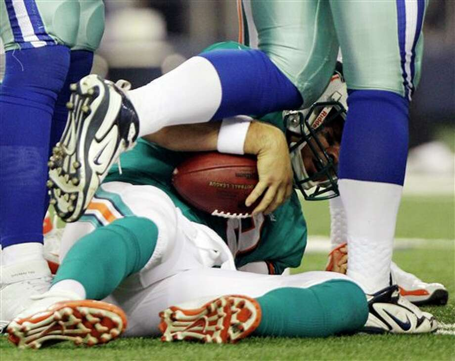 Dallas Cowboys linebacker Alex Albright, top, steps away after sacking Miami Dolphins quarterback Matt Moore (8) during the first half of a preseason NFL football game, Wednesday, Aug. 29, 2012, in Arlington, Texas. (AP Photo/LM Otero) Photo: LM Otero, Associated Press / AP