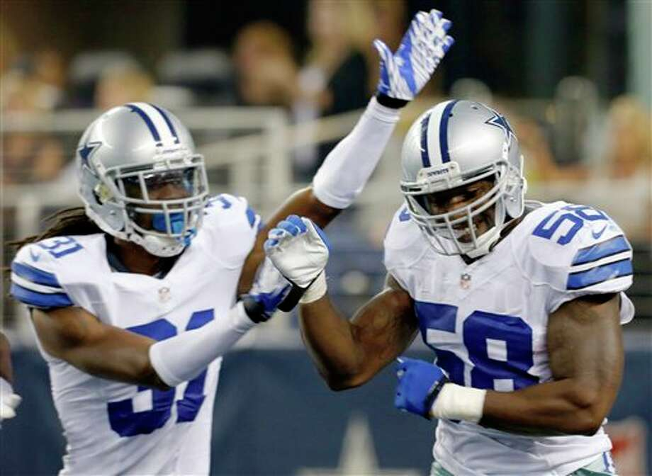 Dallas Cowboys linebacker Orie Lemon (58) celebrates after scoring a touchdown from an interception thrown by Miami Dolphins quarterback Matt Moore with Cowboys defensive back Mario Butler, left, during the first half of a preseason NFL football game, Wednesday, Aug. 29, 2012, in Arlington, Texas. (AP Photo/Sharon Ellman) Photo: Sharon Ellman, Associated Press / FR170032 AP