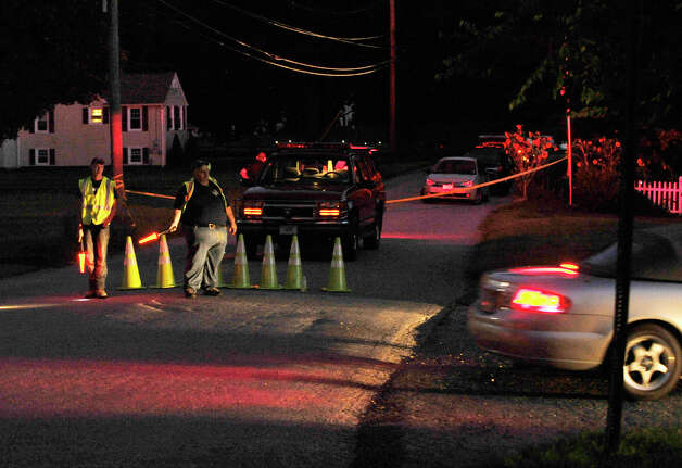 Officials direct traffic after New Milford authorities were called to the scene of an explosion at a Sunny Valley Road residence on Wednesday, Aug. 29, 2012. New Milford police say one person is confirmed dead and two others, including a child, were taken to Danbury Hospital with severe injuries. Photo: Jason Rearick / The News-Times