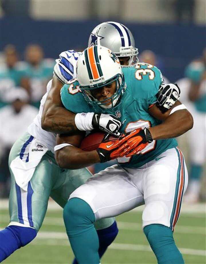 Miami Dolphins running back Daniel Thomas (33) is stopped by Dallas Cowboys' Victor Butler, rear, during the first half of a preseason NFL football game, Wednesday, Aug. 29, 2012 in Arlington, Texas (AP Photo/Sharon Ellman) Photo: Sharon Ellman, Associated Press / FR170032 AP