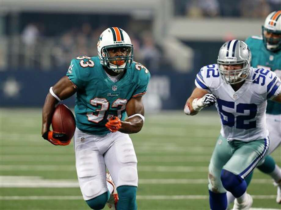 Miami Dolphins' Daniel Thomas (33) looks for running room as Dallas Cowboys' Dan Connor (52) gives chase during the first half of a preseason NFL football game Wednesday, Aug. 29, 2012 in Arlington, Texas (AP Photo/Sharon Ellman) Photo: Sharon Ellman, Associated Press / FR170032 AP