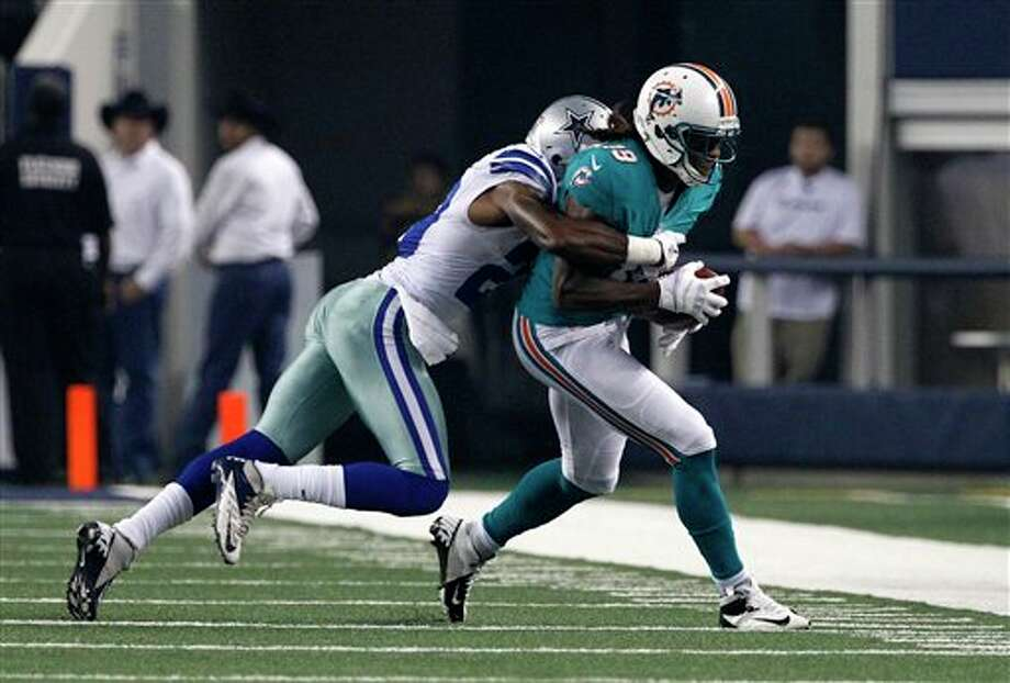 Miami Dolphins wide receiver Legedu Naanee (19) is brought down by Dallas Cowboys' Teddy Williams (20) in the first half of a preseason NFL football game Wednesday, Aug. 29, 2012, in Arlington, Texas. (AP Photo/Tony Gutierrez) Photo: Tony Gutierrez, Associated Press / AP