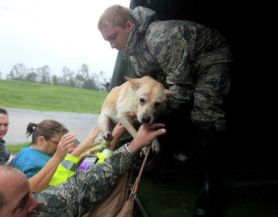 People and a dog who were rescued from their flooded homes are loaded into a Louisiana National Guard truck, after Hurricane Isaac made landfall and flooded homes with 10 feet of water in Braithwaite, La., in Plaquemines Parish Wednesday, Aug. 29, 2012. (AP Photo/Gerald Herbert) Photo: Gerald Herbert